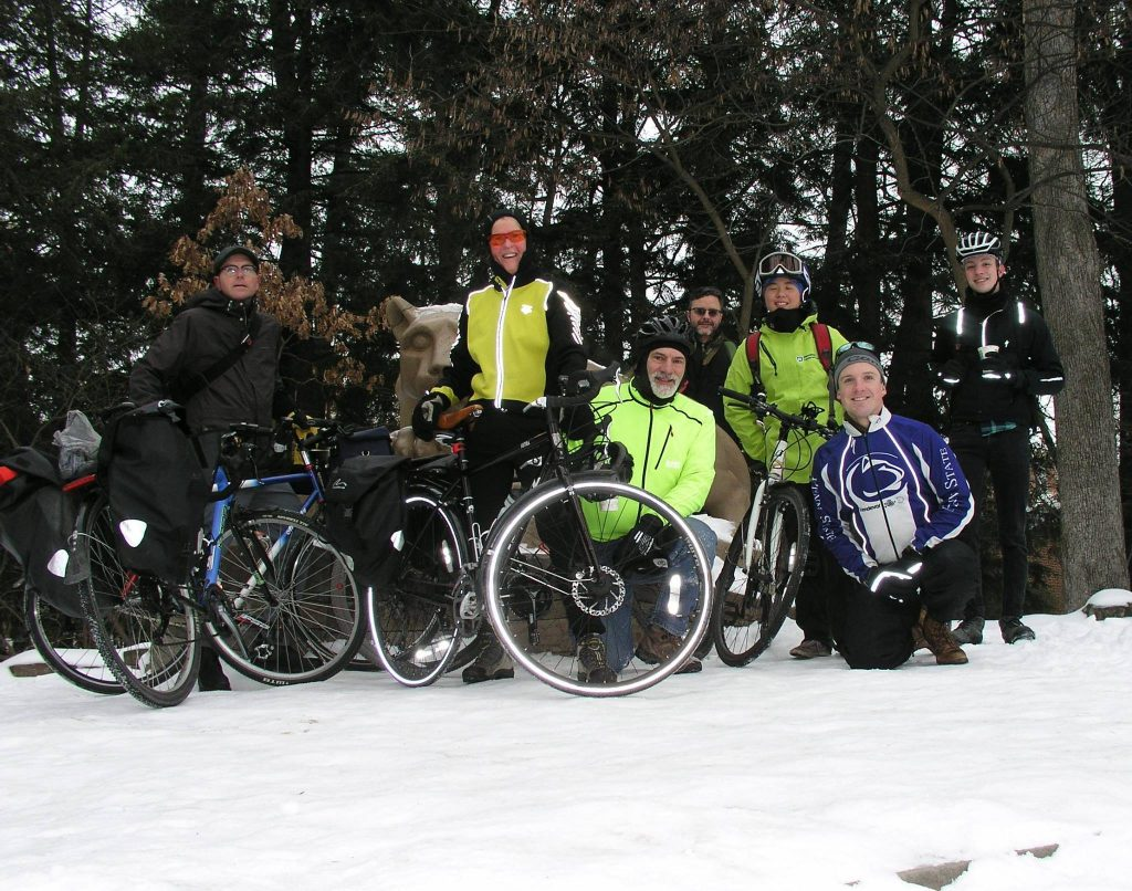 Group of CentreBike members posing with their bikes at the Nittany Lion Shrine
